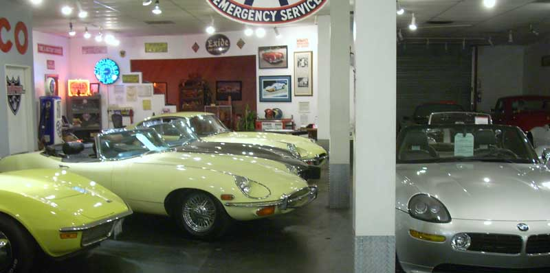 Three E-types for sale in a dealership.