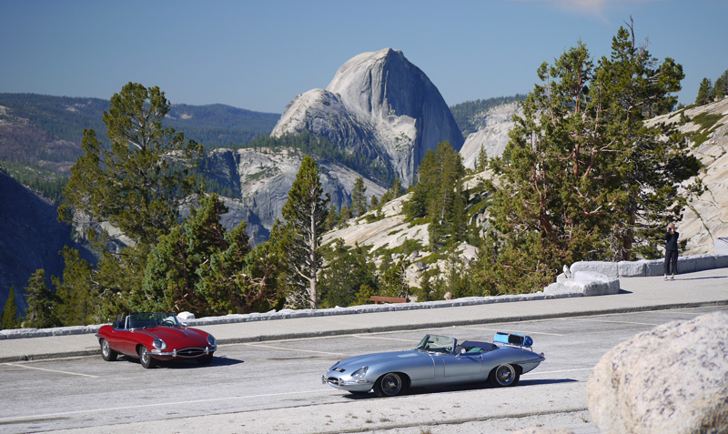 The two E-types stop at Olmstead Overlook above Yosemite Valley. Half Dome in the distance. Note what the woman on the right is photographing!