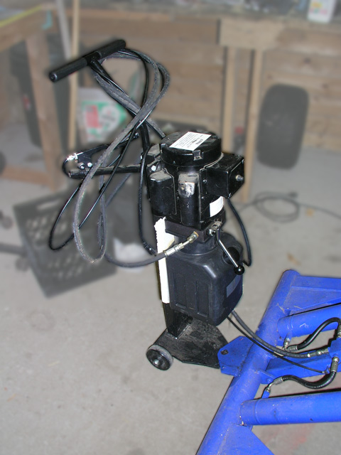 The hydraulic control unit, being used as a lever to move the entire unit around. Steel wheels are at the other end of the lift itself to facilitate movement. One person can pull or push the flat lift around on a concrete slab for repositioning or storage.
